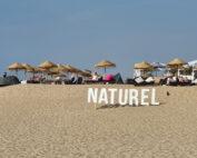 Op het strand van Scheveningen staan grote witte letters van NATUREL. De lucht is blauw en op de achtergrond zie je ligplekken met houten parasols