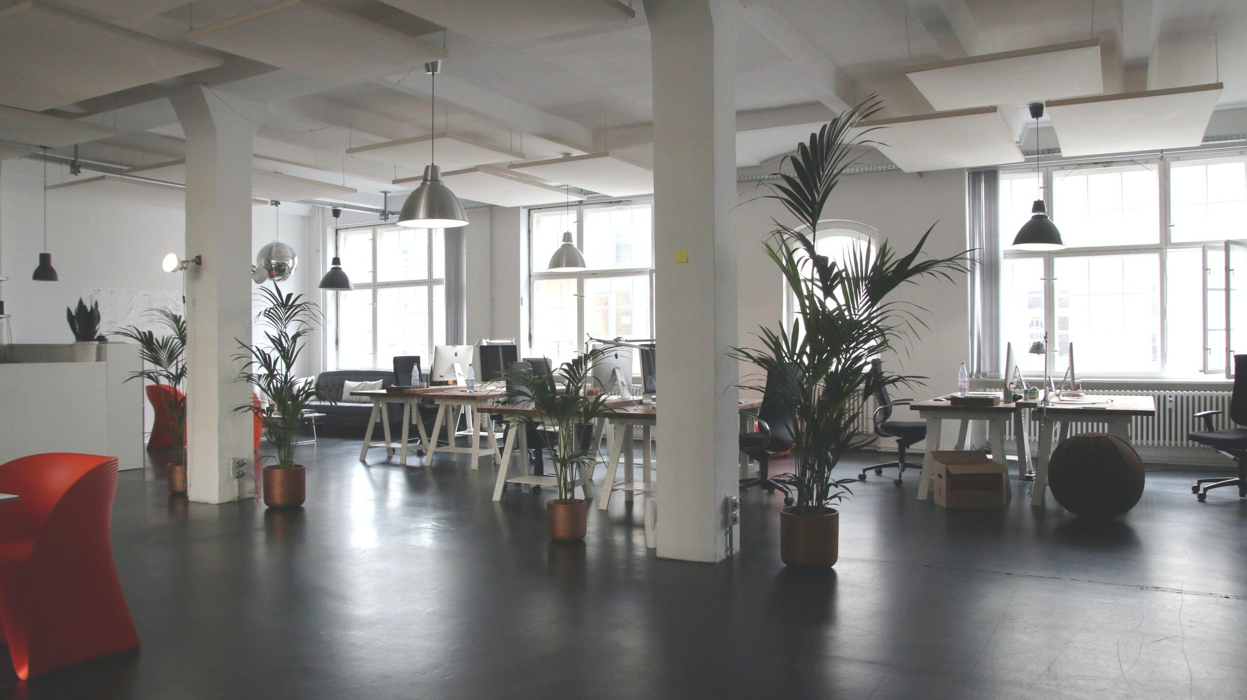 Een kantoorruimte met ene hoog plafond en tafels en stoelen.